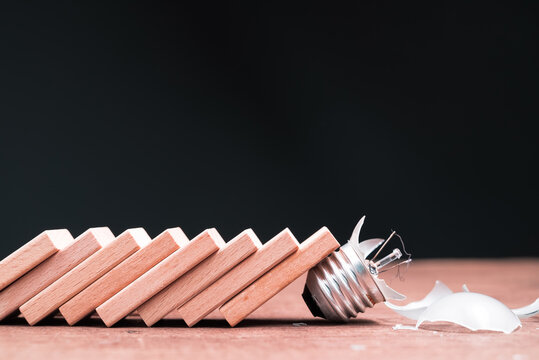 Domino effect shatter the light bulb, business idea fail, caused by the external factor and economic, business going down in crisis