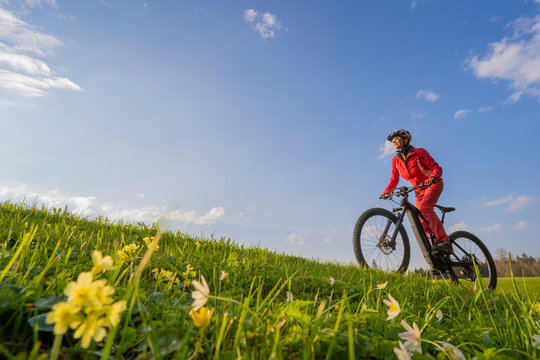 pretty mid age woman riding her electric mountain bike in early springtime in the Allgau mountains near Oberstaufen, in warm evening light with blooming spring flowers in the Foreground