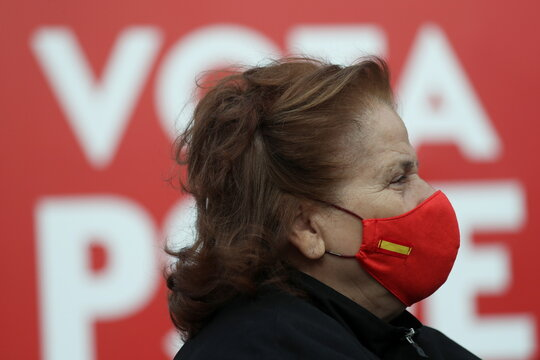 A woman wearing a face mask with the Spanish flag attends a Spanish Socialist Workers' Party (PSOE) campaign rally for Madrid's upcoming regional elections in Alcorcon