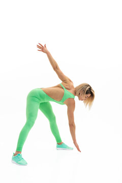 full body portrait of young sporty woman stretching before exerc
