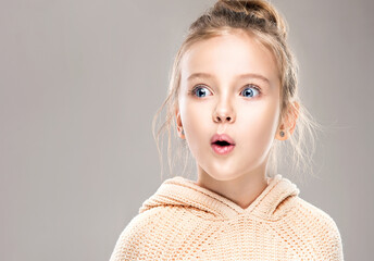 The child is a beautiful girl with wide eyes, look away in surprise. Baby in a knitted sweatshirt ....