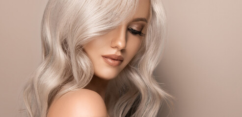 Beautiful girl with hair coloring in ultra blond. Stylish hairstyle curls done in a beauty salon....