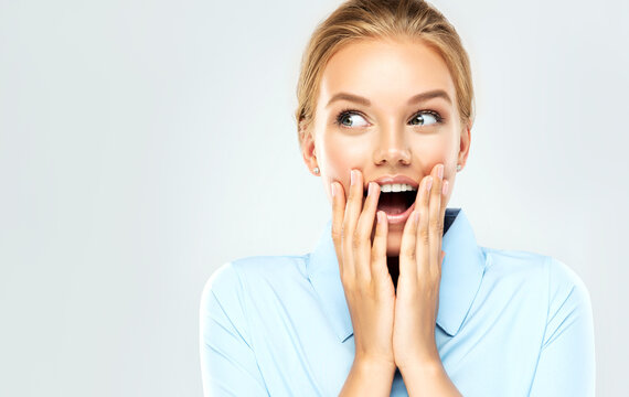 Woman  happy and surprised shouts holds cheeks by hand .Beautiful girl  in a blue shirt  pointing to looking right . Presenting your product. Expressive facial expressions