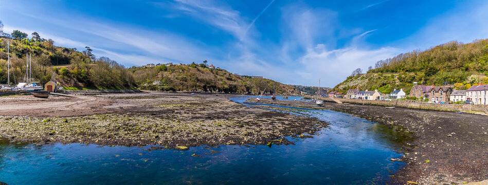 A panorama view at low tide across Lower Fishguard harbour, South Wales on a sunny day
