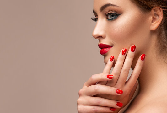 Beautiful woman showing red lips and   manicure nails .Blue eyed  model girl .  Evening bright makeup . Beauty , make-up and cosmetic