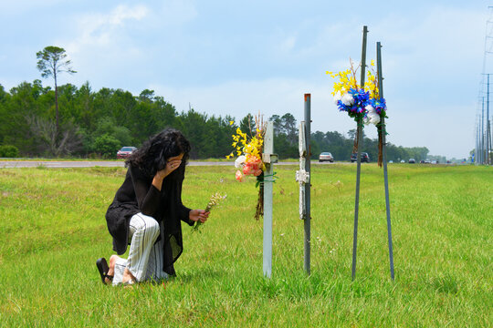 A grieving bereaved woman kneeling down to placing flowers on crosses beside a busy road marking the location of where her friend was killed in a terrible drunk driver car wreck.