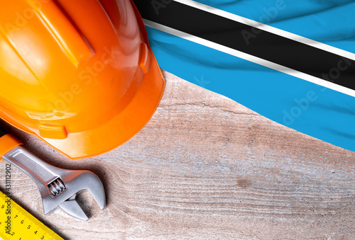 Botswana flag with different construction tools on wood background, with copy space for text. Happy Labor day concept.