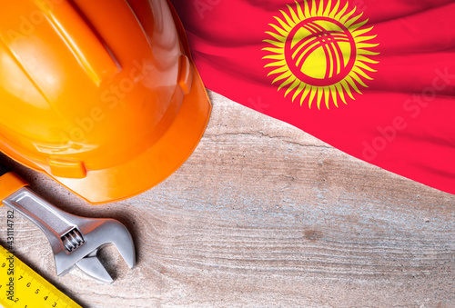 Kyrgyzstan flag with different construction tools on wood background, with copy space for text. Happy Labor day concept.
