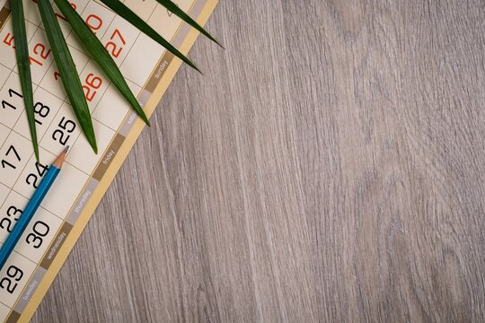 Calendar sheet, palm leaf and pencil on wood table texture. Business and planning