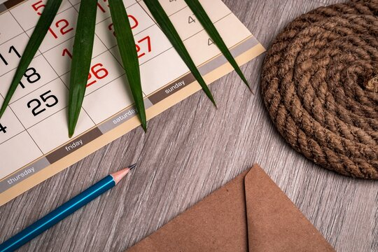 Palm leaf, calendar, pencil and envelope from old paper on a wooden table texture. Business and planning