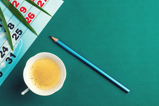 Palm leaf, calendar, coffee cup and pencil on green table surface. Business and planning