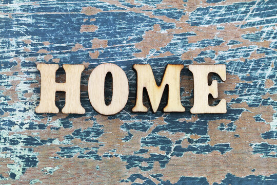 Word home written with colorful wooden letters on rustic wooden surface and colorful flowers