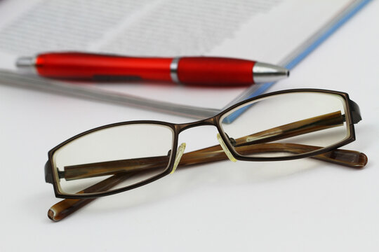 Glasses with newspaper and pen in the background