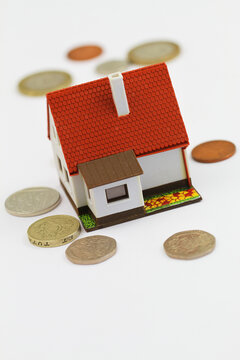 Model house with British pound coins scattered around it on white background