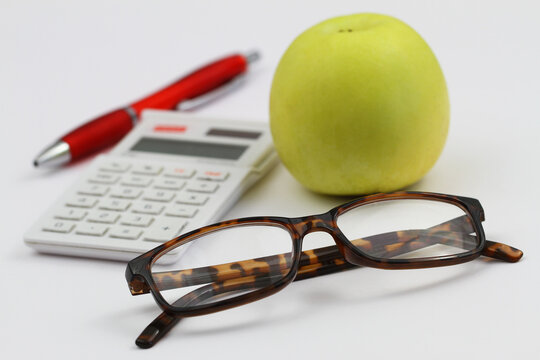 Reading glasses, calculator, pen and apple on white background