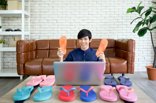 Young asian man sells various styles of rubber slippers online via application on laptop computer. Small home business concept.