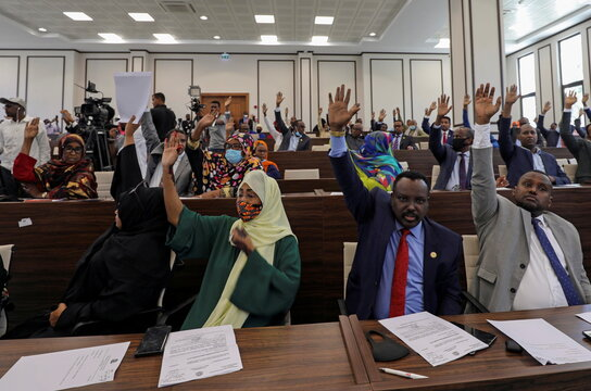 Somalia legislators vote by rising their hands to cancel a divisive two-year presidential term extension, inside the lower house of Parliament in Mogadishu
