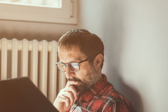Contemplative man reading a book at home, sitting by the window