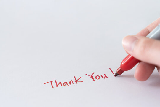 Hand writing thank you note using red marker pen