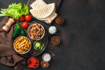 French fries, fried chicken, vegetables and pita bread on a brown background with space to copy. Ingredients for shawarma, burritos, gyros.