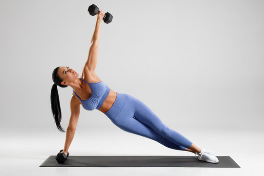 Fitness woman doing side plank exercise on gray background. Athletic girl working out with dumbbells