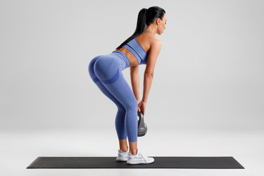 Fitness woman doing deadlift exercise for glutes on gray background. Athletic girl working out with kettlebell