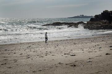 Samotna kobieta idąca plażą Polstreach w Kornwalii