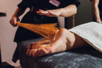 massage of female feet with bamboo sticks.