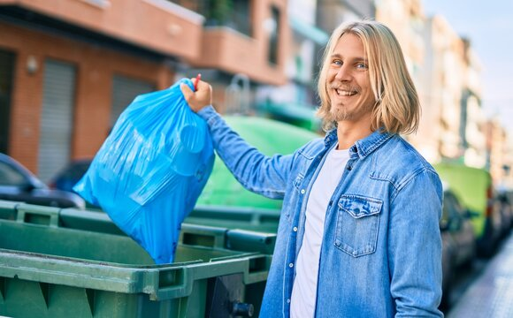 Young blond scandinavian man throwing waste bag to the container at the city.