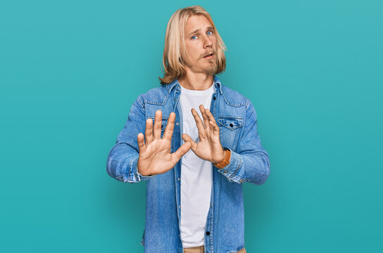 Caucasian man with blond long hair wearing casual denim jacket moving away hands palms showing refusal and denial with afraid and disgusting expression. stop and forbidden.