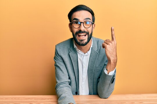 Young hispanic man working at the office pointing finger up with successful idea. exited and happy. number one.
