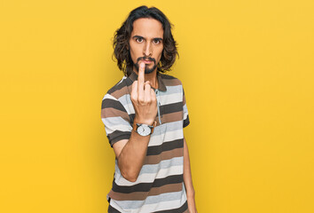 Fototapeta Young hispanic man wearing casual clothes showing middle finger, impolite and rude fuck off expression