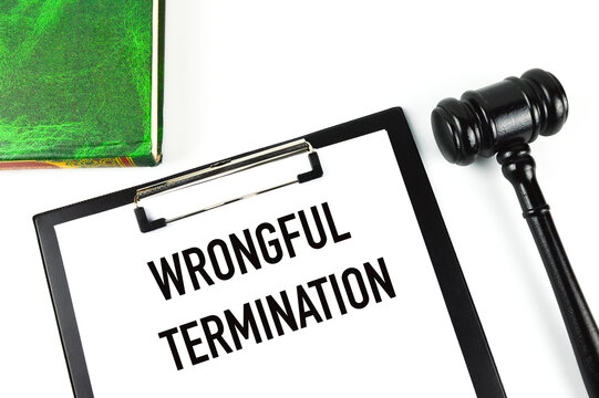 Green book, judge gavel and white paper written with WRONGFUL TERMINATION