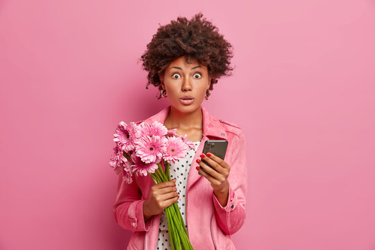 Photo of surprised female model holds bouquet of flowers modern smartphone receives unexpected congratulation on birthday dressed in stylish clothes. Women spring time special occasion concept