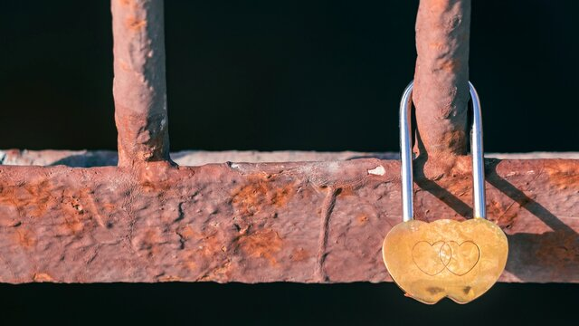 Golden lock with hearts close-up on the metal fence of the bridge. Love, family