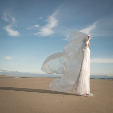 bride on beach in conceptual portrait holding sheet of plastic