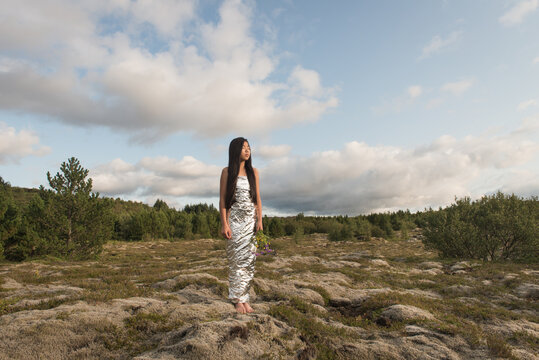 young woman in silver dress standing in a lava field in Iceland