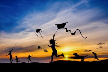 Fototapeta Grupa dzieci puszczających latawca o zachodzie słońca obraz
