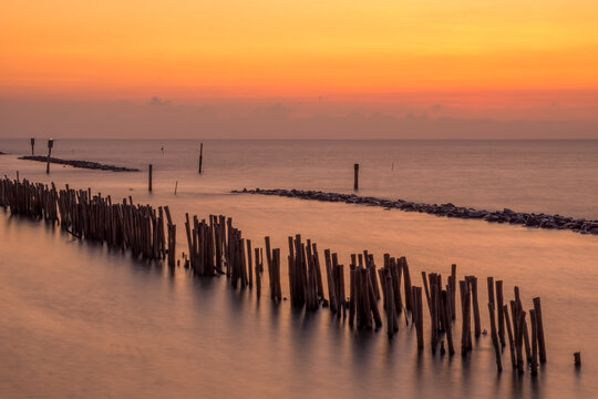 Bamboo wall and stone wall for protection against ocean waves. Sunset at the sea, Samut Sakhon, Thailand