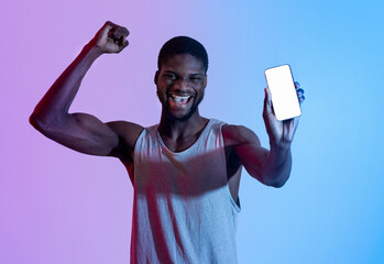 Excited black athlete showing cellphone with blank screen, making YES gesture in neon light, mockup for design