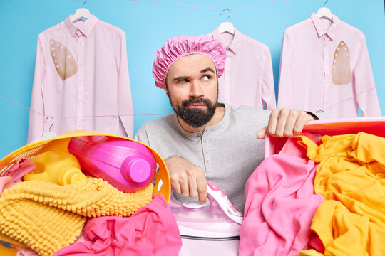 Thoughful busy househusband wears bath hat and casual jumper surrounded by piles of laundry uses electric iron stands near board concentrated away being deep in thoughts. Domestic routines concept