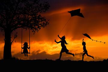 Obraz Sylwetki dzieci bawiących się latawcami i na huśtawce - fototapety do salonu