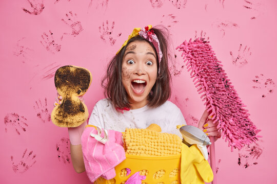 Emotional cheerful housewife exclaims loudly rubs dust in room holds dirty sponge and mop does laundry tidies up house poses against pink background. Spring cleaning domestic chores concept.
