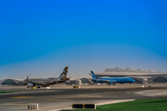 Abu Dhabi, UAE, March 2021, Etihad Airbus A320 is taxiing for departure while Etihad B787 Dreamliner in special livery is taking off at Abu Dhabi International Airport, new terminal in background