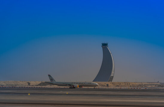 Abu Dhabi, United Arab Emirates, March 2021, Abu Dhabi International Airport with new modern Control Tower behind a  Boeing 777 airplane stored due to coronavirus pandemic