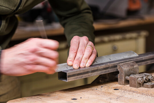 Mechanic measuring metal bar before sawing it