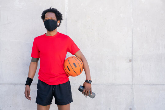 Afro athletic man holding basketball ball.