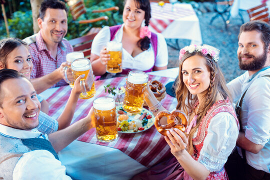Group of people in proper Tracht drinking in Bavarian beer garden