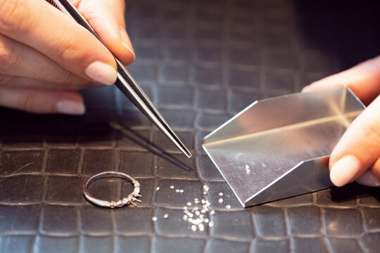 Jeweler sorting thru little diamonds in her workshop