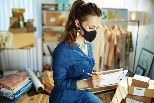 modern small business owner woman with black mask in office